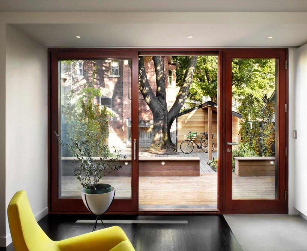 Một cửa kính lớn mở ra để lộ ngôi nhà tiếp cận bên ngoài
