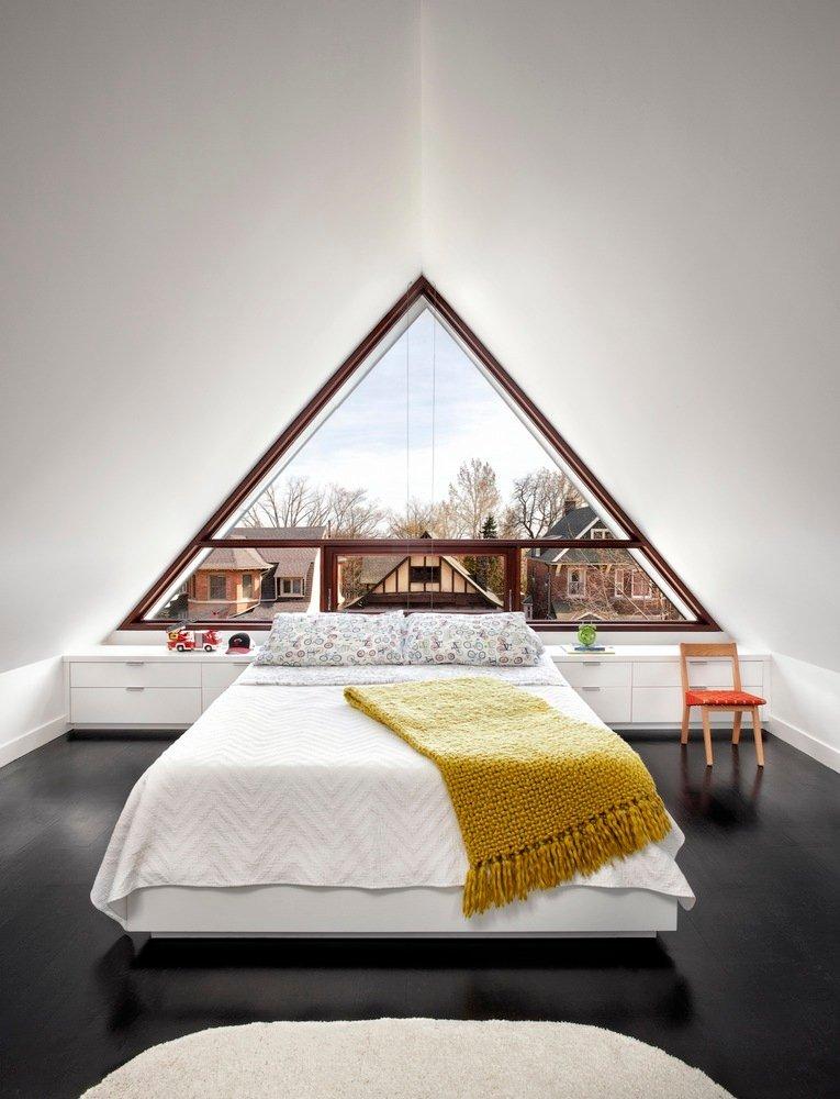 một cửa sổ kính hình tam giác rộng mở ra tầm nhìn của khu phố