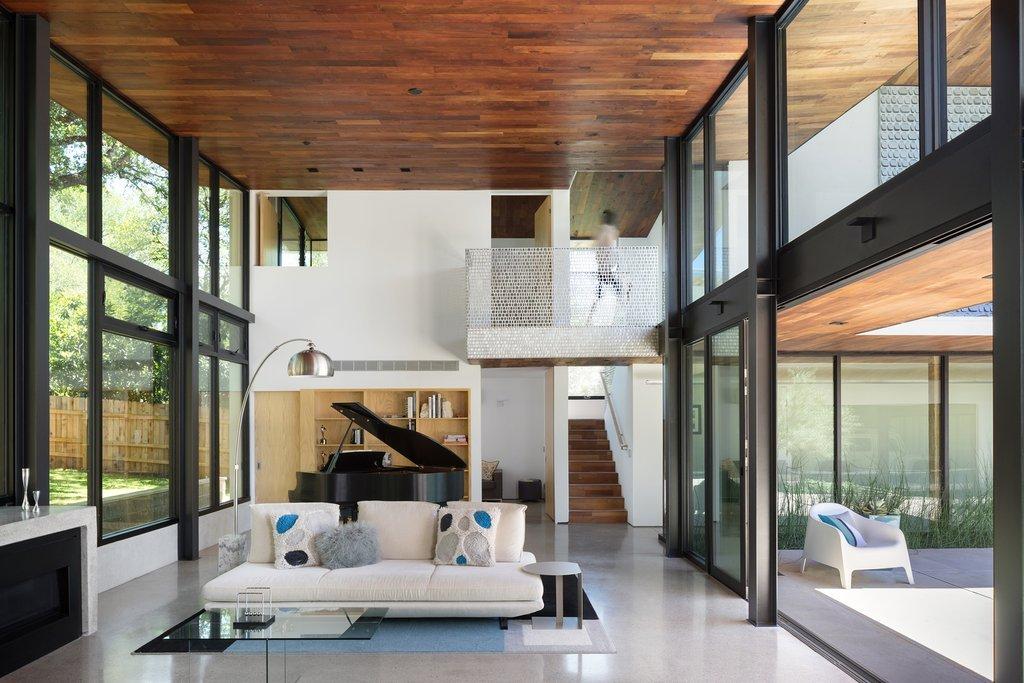 Một phòng khách có chiều cao gấp đôi với cửa chớp di động để kiểm soát ánh nắng mặt trời